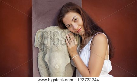 Young Woman Is Embracing The Ancient Hanuman Statue.
