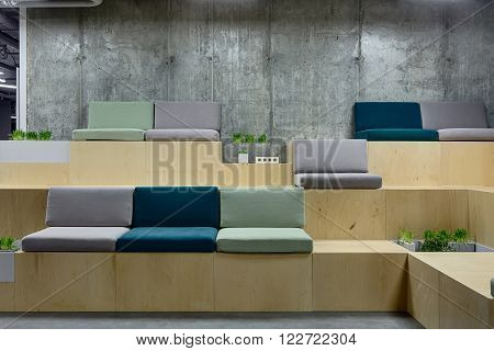 Light wooden benches with multi-colored seats. Seats are made up of pillows. Benches are decorated with grass, plants and bricks. On the background there is a concrete wall. On the floor there are gray tiles. Place for coworking.