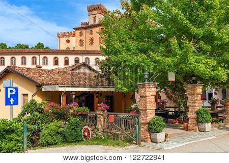 Small outdoor restaurant and old medieval castle on background in town of Barolo, Piedmont, Northern Italy.
