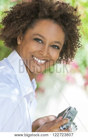 A beautiful mixed race African American girl or young woman looking happy taking pictures or photographs outside with a retro digital camera