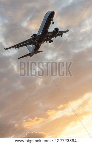 A modern commercial airplane or airliner flying at sunrise or sunset