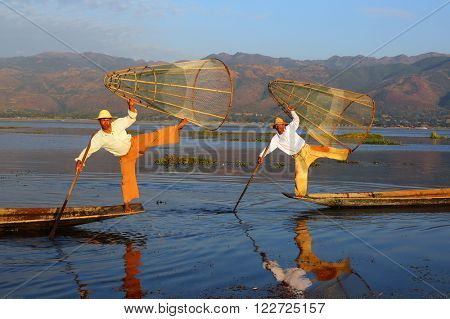 Myanmar travel attraction landmark - Traditional Burmese fishermen with fishing net at Inle lake in Myanmar famous for their distinctive one legged rowing style