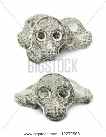 Skull shaped salt coated licorice candy isolated over the white background, set of two different foreshortenings
