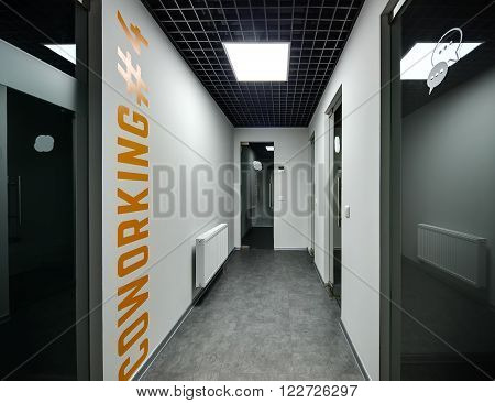 Glass doors on either side of the corridor with white walls. On the left wall there is an orange inscription Coworking 4. Also on the left wall there is a radiator. Ceiling is dark with one lamp. On the floor there are gray tiles. Some parts of the corrid