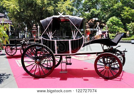 some black carriage with a background in garden