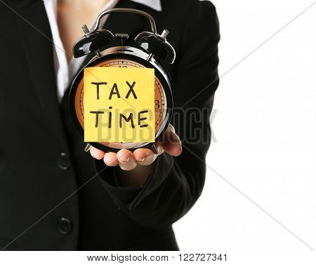Woman in black suit holding alarm with tax time inscription, isolated on white