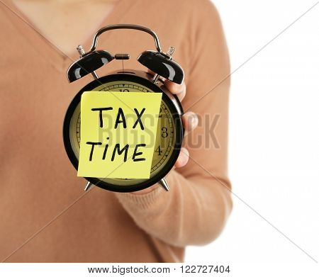 Woman in brown sweater holding alarm with tax time inscription, isolated on white