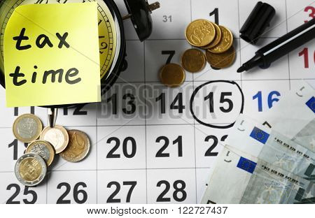 Tax time on alarm clock with euro, marker and calendar
