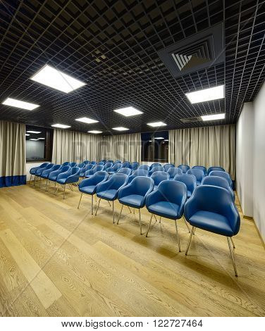 Lecture room in a coworking. There are a lot of blue chairs. On the background there are brown windows and curtains. Walls are white. On the floor there are light parquet. Ceiling is dark with rectangular lamps.