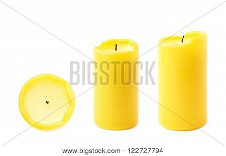 Burned yellow wax candle isolated over the white background, set of three different foreshortenings