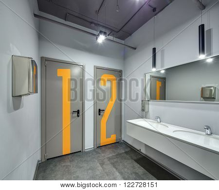 Washroom with light walls. On the back wall there are two gray doors with 1 and 2 orange numbers on them. On the right wall there are two white sinks, a wall-mounted soap dispenser and a mirror. On the left wall there is a paper towel dispenser. One door