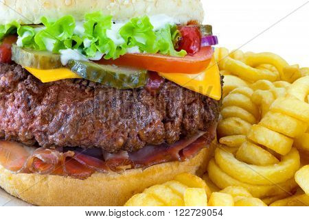 Hamburger with Fries / Detail of hamburger with bacon green salad tomato cheese cucumber onion sauces and curly french fries. Isolated on white