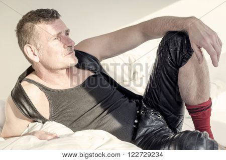 man in black fetish leather gear lying in bed