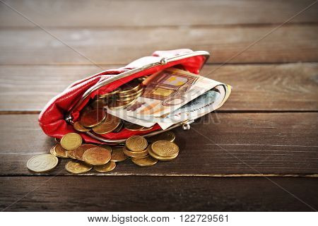 Purse with euros and coins on wooden background