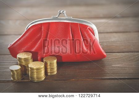 Red leather purse and stacked coins on wooden background