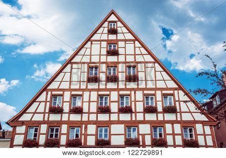 Beautiful bavarian house with flower pots and cloudy blue sky Schwabach Germany. Architectural theme.