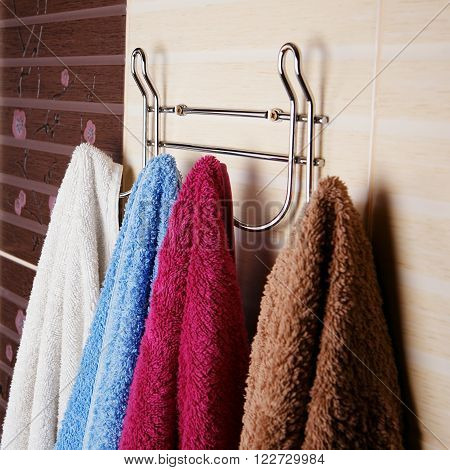 Colored Towels Hanging On The Rack In The Bathroom.