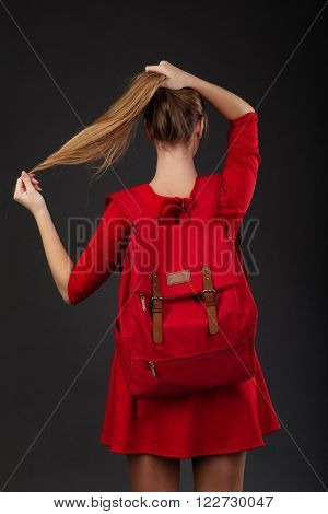 Portrait Of A Girl In Red Dress, With A Big Red Backpack