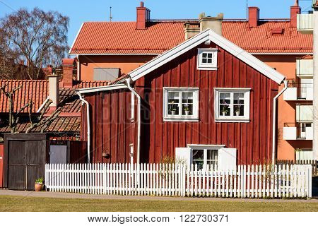 Kalmar Sweden - March 17 2016: An old red wooden house in the middle of the city with modern buildings in the background. White fence in front of house.