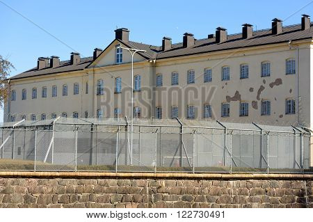Kalmar Sweden - March 17 2016: The prison building with the exercise yard and surrounding barbed and netted fence. People walking on inside of the fence. Real people in everyday life.