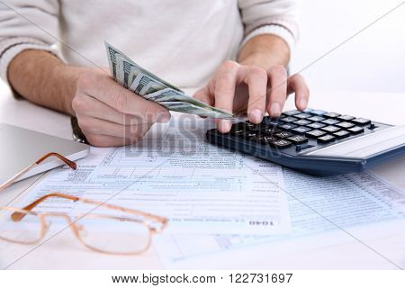 Man counting money with calculator at the table