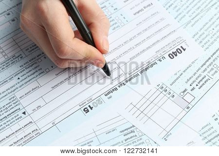 Female hand holding a black pen and filling in the 1040 Individual Income Tax Return Form for 2015 year, close up