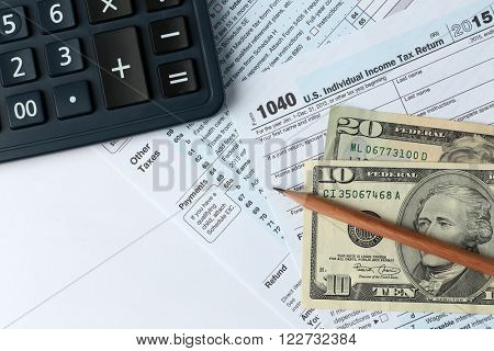 1040 Individual Income Tax Return Form for 2015 year with a pencil to fill in, calculator and dollar bills on the white desk, top view