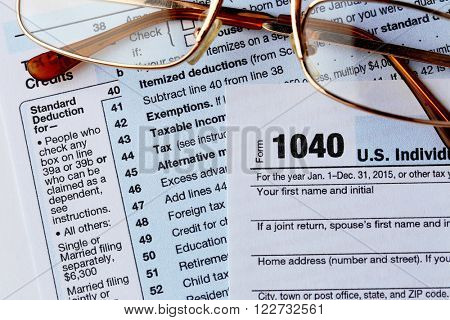 1040 Individual Income Tax Return Form with  metal rimmed glasses on the white desk, close up