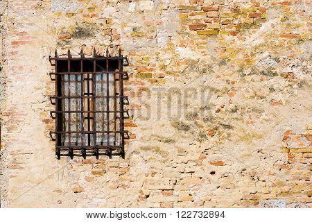 Detail of a window with an old and rusty grating on a old wall with bricks. San Gimignano, Siena, Tuscany, Italy