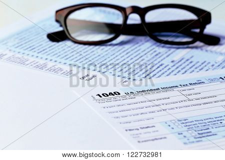 1040 Individual Income Tax Return Form with  black rimmed glasses on the white surface, close up