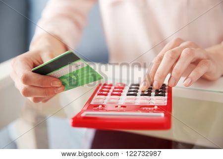 Female calculate with credit card, closeup