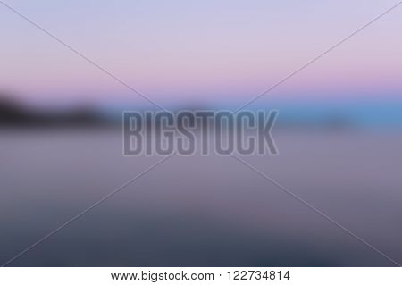 Blurred unfocused nature background mountains, sea and twilight sky in scarlet, pink, purple, azure colours