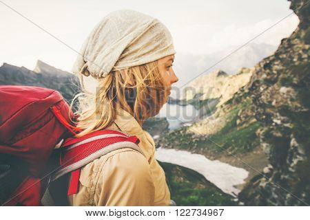 Young Woman with red backpack hiking alone Travel Lifestyle concept lake and mountains landscape on background Summer vacations outdoor. windy soft focus
