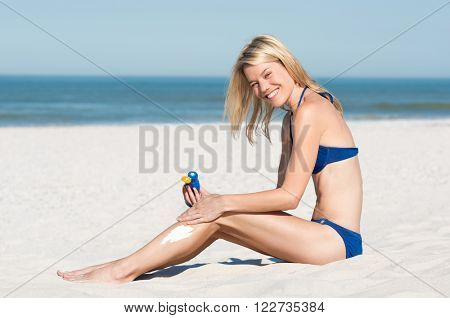Young woman in blue bikini sitting on sand and applying suntan lotion before sunbathing. Smiling young woman applying sunscreen on beach.