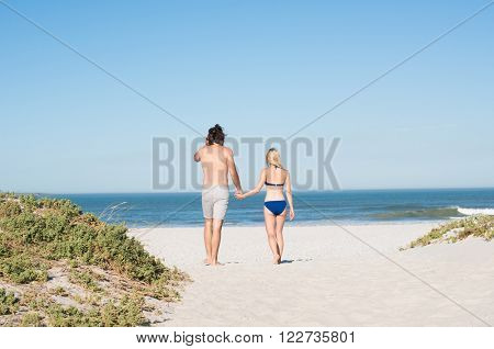 Young couple holding hands walking towards sea. Young couple walking on a sandy beach towards the coastline. Romantic young couple on the beach walking along the shore.