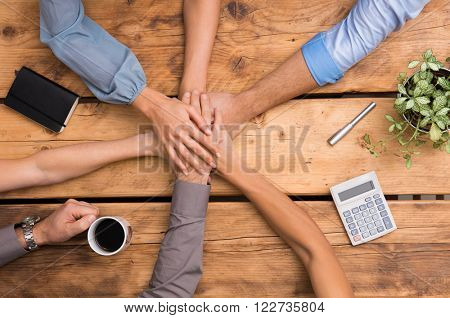 Closeup of business colleagues with their hands stacked. Business team showing unity with their hands together. Close up of business partners making pile of hands at meeting. Business team work.