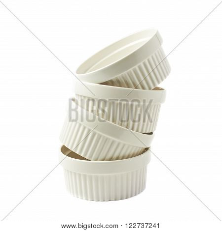 Pile of multiple white porcelain souffle ramekin dishes isolated over the white background