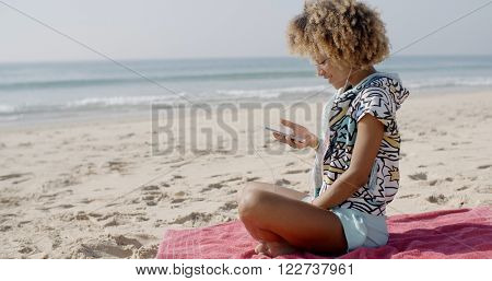 Woman Listening To Music On The Beach