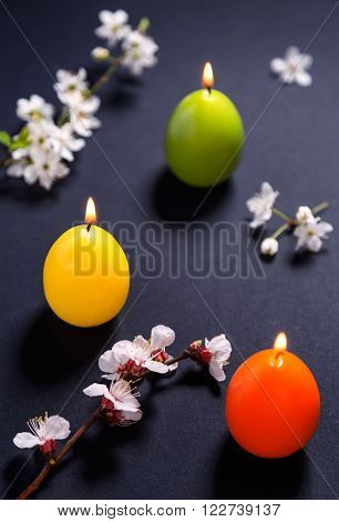 Colored candles in the shape of Easter egg with flowers pattern