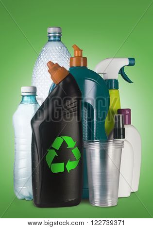 Set of different plastic containers on green background with the recycle sign on the front one