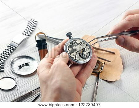 Watchmaker hands repairing mechanism of old watch closeup