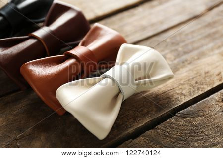 A set of leather bow ties lined on a brown wooden background