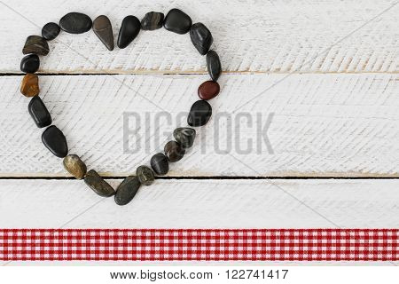 Heart shaped dark shades of stone, small pebbles arranged as a heart on white wooden background with red checkered ribbon