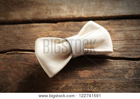 White leather bow tie on a brown wooden background