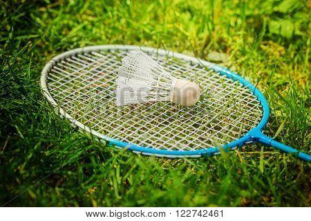 Shuttlecock and badminton racket on green grass