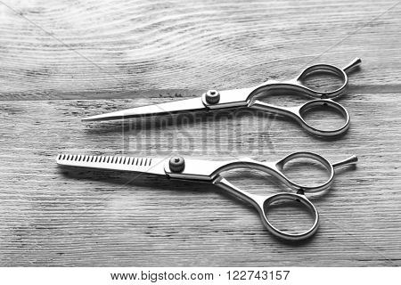 Two professional metal scissors lying beside each other on wooden table, close up