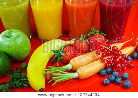Colorful fresh pressed fruit green yellow oragne and red juices with fresh fruits and berries on black and red background