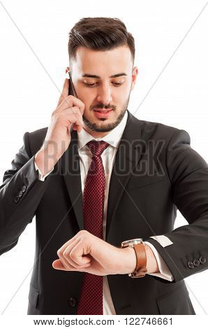Business Man Talking On The Phone While Checking His Watch