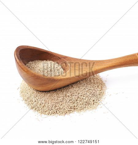 Wooden spoon over the pile of dry yeast isolated over the white background