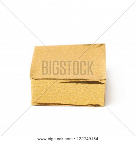 Single bouillon stock broth cube wrapped in golden foil, composition isolated over the white background